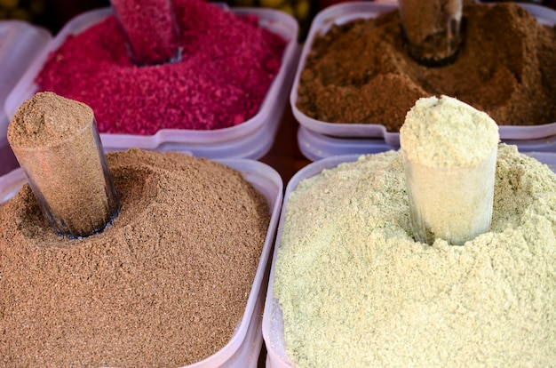 Spices on the market in white containers.