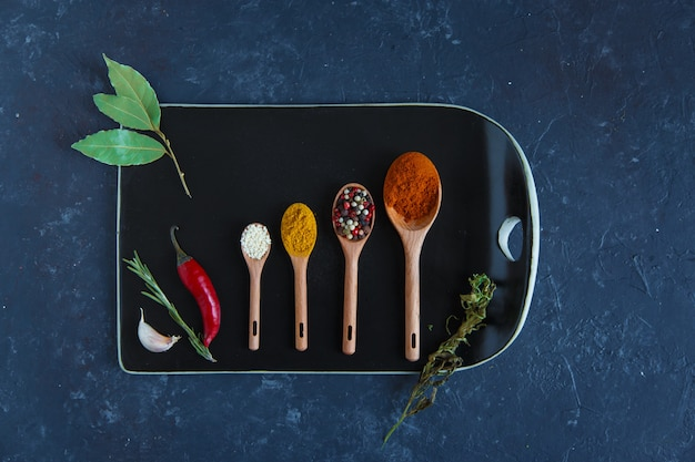 Spices in measuring spoons and herbs on a cutting board.
