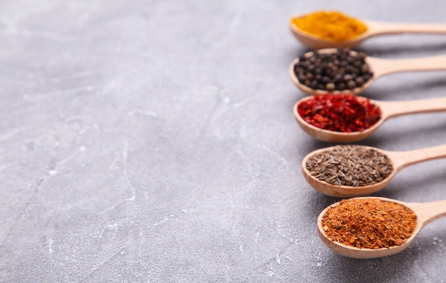 Spices mix on wooden spoons on a grey background. top view