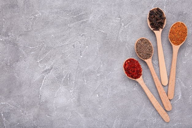 Spices mix on wooden spoons on a grey . top view