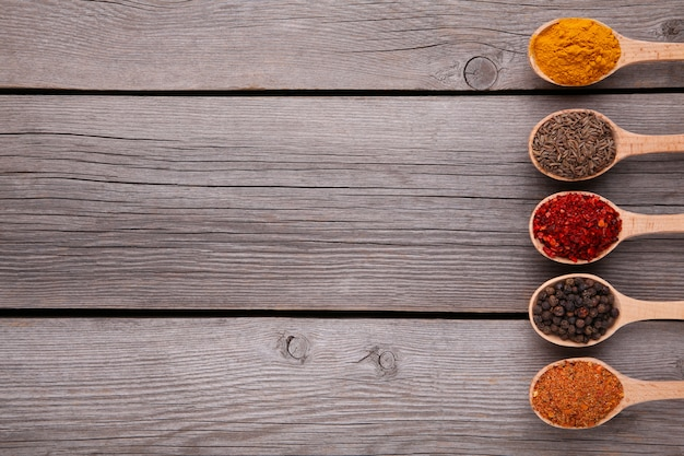 Spices mix on wooden spoons on a grey wooden background. top view