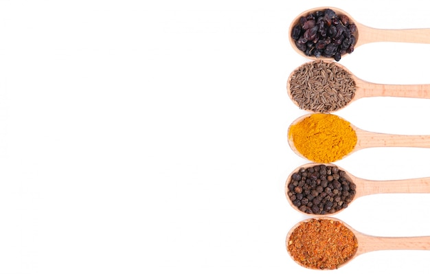 Spices mix on wooden spoons isolated on a white background. top view