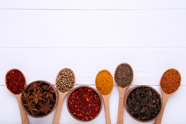 Spices mix on wooden spoons on a white wooden background. top view