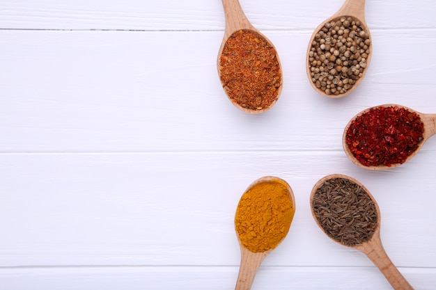 Spices mix on wooden spoons on a white wooden table. top view