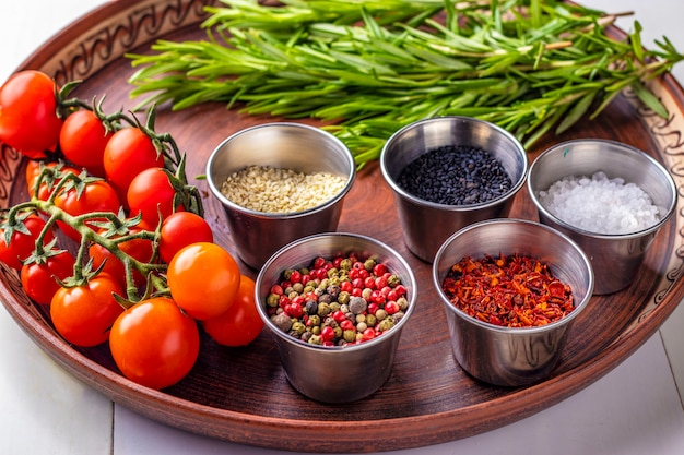 Spices: a mixture of peppers, paprika flakes, sea salt, black and white sesame, rosemary and cherry tomatoes on a plate close-up