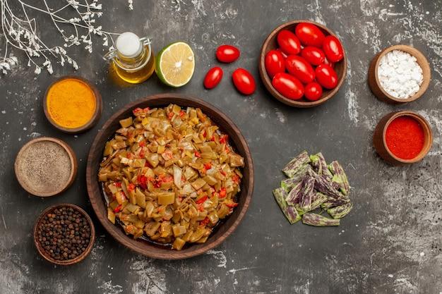 テーブルの上のスパイスサヤインゲンの隣のボウルに油のカラフルなスパイスとトマトのレモンボトル