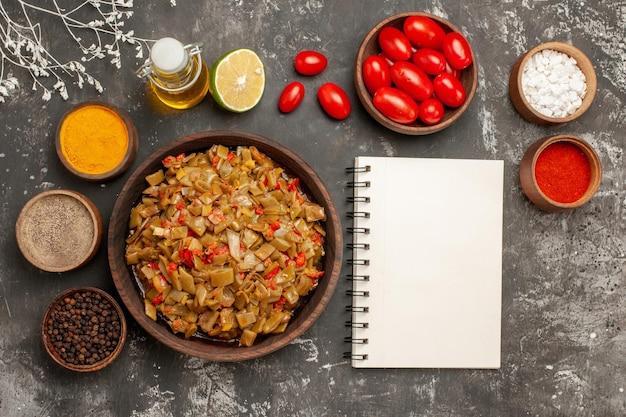 テーブルの上のスパイス白いノートと木の枝の横にあるボウルにオイルのカラフルなスパイスとトマトのレモンボトル