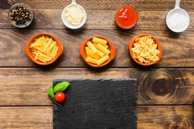 Spices and pasta near board