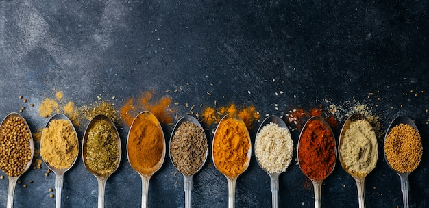 Spices in spoons background. varieties of spices (turmeric, pepper, chili, coriander, cinnamon) and peppers for cooking. culinary food concept.