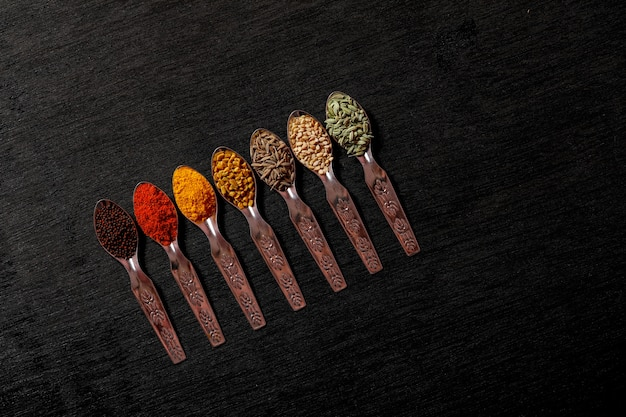 Spices in spoons on black background