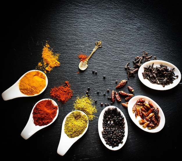 Spices in the spoons over a black stone