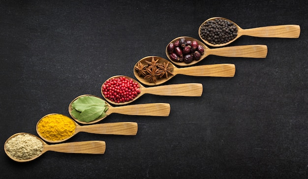 Spices in spoons over black table background. top view of season