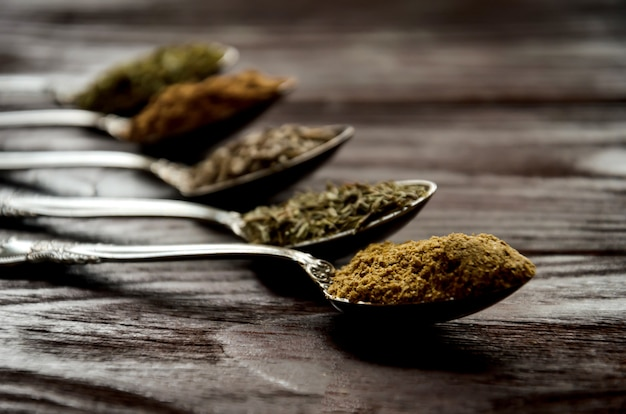 Spices in spoons - coriander, cumin, thyme, provencal herbs, ground nutmeg