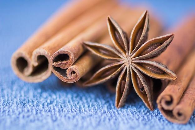 Специи: звездчатый анис и палочки корицы на синем столе. крупный план. размытие
