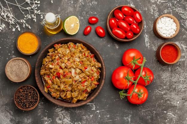 Spezie sul tavolo piatto di fagiolini limone bottiglia di olio spezie accanto ai pomodori sul tavolo scuro