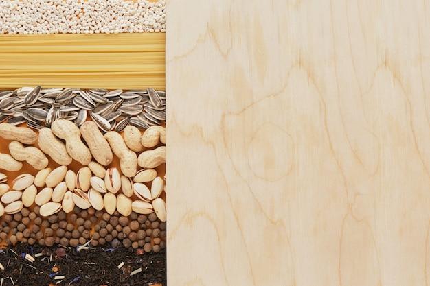 スパイス、お茶、シリアル、ナッツ、種子、パスタのテクスチャ、テキストコピースペースのモックアップ用の木製ボード、食料品のコンセプトの上面図