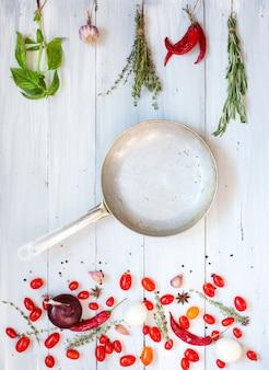 Специи, овощи и сковорода с копией пространства на деревянном. книга рецептов. плоская планировка.