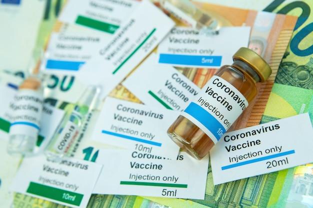 Колос на медицинских изделиях. нехватка лекарств и медикаментов в условиях эпидемии коронавируса. covid-19. доллары сша, этикетки вакцины на синем фоне.