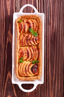Spicy apple tart on plate over wooden table