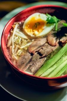 Острый азиатский сычуаньский суп с лапшой, говядиной, яйцом и огурцом в миске.