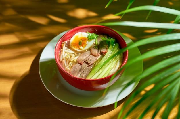 Острый азиатский сычуаньский суп с лапшой, говяжьим фаршем, яйцом и огурцом в миске.
