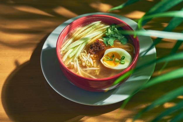 Острый азиатский сычуаньский суп с лапшой, фаршем, яйцом и огурцом в миске.