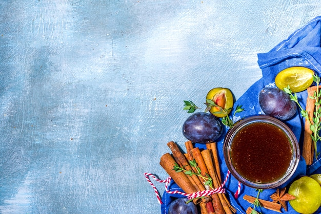 Spicy autumn plum jam in small jar, with cinnamon, thyme, anise and fresh plums on concrete blue background copy space
