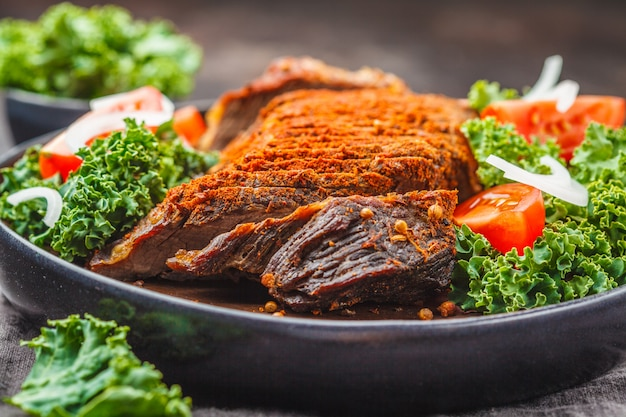 Spicy baked beef with kale salad in black plate on dark background.