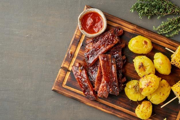 Пряные свиные ребрышки барбекю, кукурузные колосья и измельченный картофель. американская кухня. вид сверху, копия пространства