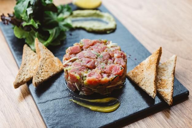 Острый тартар из тунца с голубым соусом и острым соусом. подается с тостами и салатом на черной каменной тарелке.
