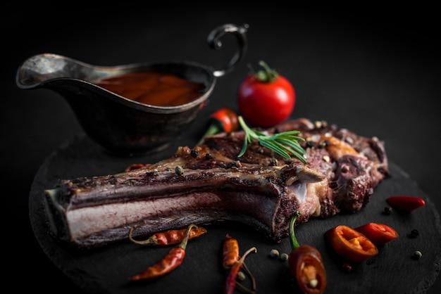매운 뼈가 들어간 립아이 스테이크는 칠리 파퍼와 토마토 소스를 어두운 배경에 곁들였습니다. 검은 돌 접시에 육즙 구운 스테이크