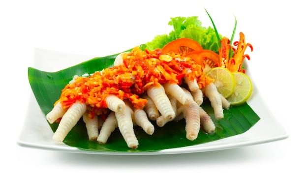 Острые куриные ножки с соусом чили самбал, популярное в индонезии, малайзии и сингапуре, украшение из резных овощей, вид сбоку