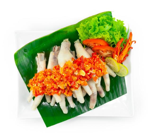 Острые куриные ножки с соусом чили самбал, популярное в индонезии, малайзии и сингапуре. украшение из резных овощей.