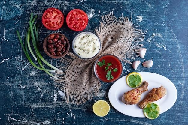 Carne di pollo piccante in un piatto bianco con ingredienti intorno.