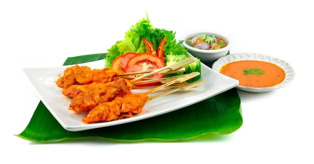 Острый куриный сатей или острый цыпленок-гриль на шпажках, подается с арахисовым соусом с чили, кисло-сладким соусом. тайская еда, закуска, украшение блюда с резьбой по овощам, вид сбоку