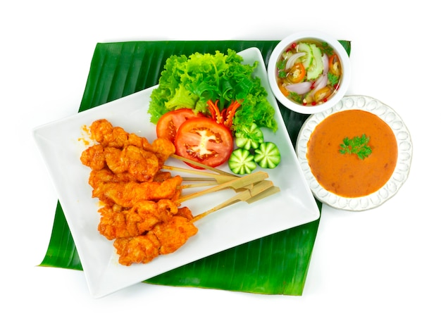 Острый куриный сатей или острый цыпленок-гриль на шпажках, подаваемый в арахисовом соусе с чили, кисло-сладком соусе тайская еда, закуска, украшение блюда с овощами нарезкой сверху
