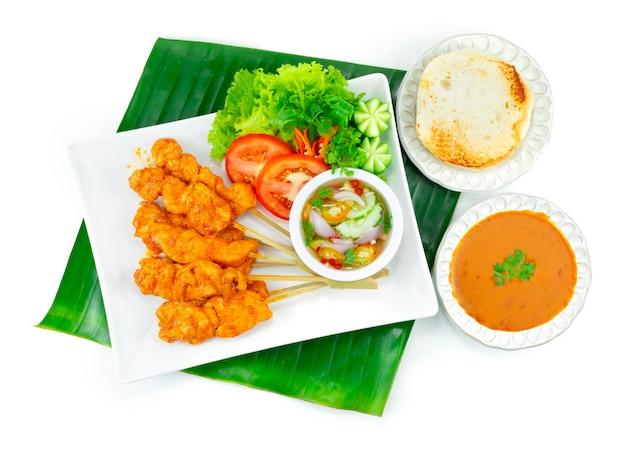 Пикантный куриный сатей или пикантный цыпленок-гриль на вертеле подаются на гриле хлеб с арахисовым соусом чили, кисло-сладкий соус тайская еда закуска украшение блюда с овощами нарезкой сверху