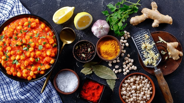 Spicy chickpea curry with ingredients on a dark concrete background: