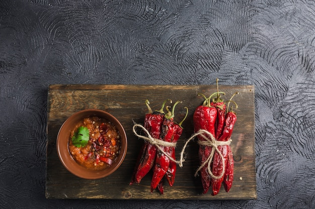 Spicy chili on a dark background in ceramic plates on a wooden board