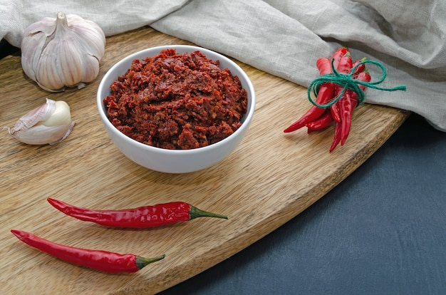 Spicy chili on a dark table in ceramic plates on a wooden board, flatlay. used as an ingredient for harissa, ajika, muhammara. east and middle east kitchen.