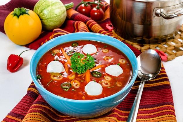 Zuppa di pomodoro piccante al peperoncino con palline di panna acida in una ciotola