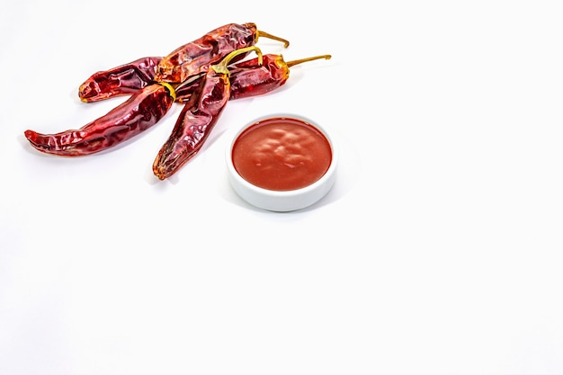 Spicy chili sauce in bowl with hot chili peppers