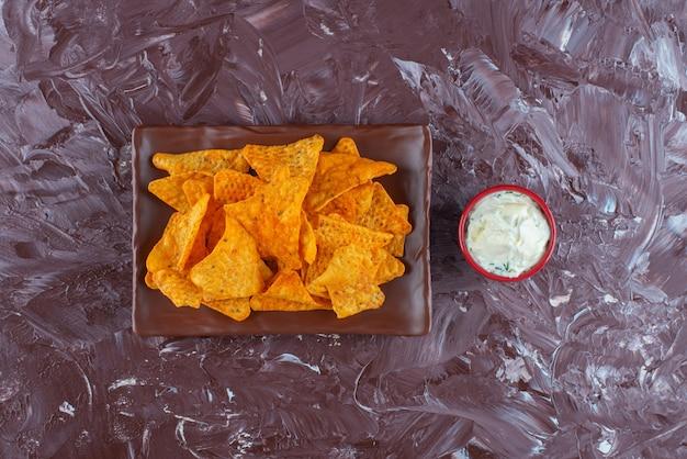 대리석 표면에 마요네즈 그릇 옆 접시에 매운 칩