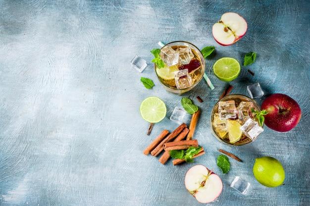 スパイシーなシナモンアップルアイスティーまたはレモネードカクテル、夏の飲み物、青い背景