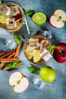スパイシーなシナモンアップルアイスティーまたはレモネードカクテル、夏の飲み物、青いテーブル