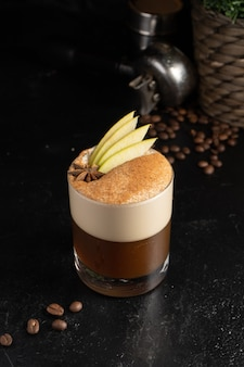 Spicy coffee with an apple in a transparent glass. hot coffee drink made from espresso, milk foam, apple slices, cinnamon and star anise.