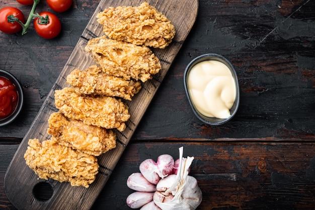 매운 깊은 튀김 빵 가루 입힌 닭 날개는 오래 된 어두운 나무 테이블, 평면도에 잘라냅니다.