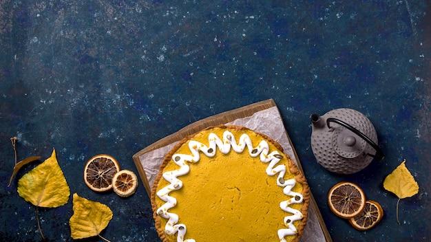 Spicy delicious round pumpkin pie decorated with white cream and pumpkin seeds