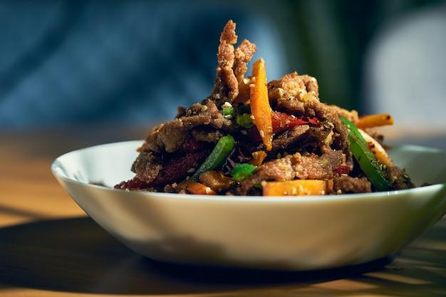 Острая сухая сычуаньская говядина вок с перцем, семенами кунжута, морковью и зелеными помидорами в белой миске. китайская кухня