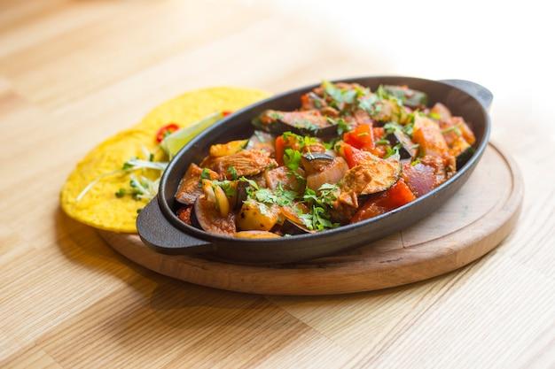 Пряный фахито в чугунной сковороде и кукурузные лепешки на деревянный стол. мексиканская еда. мексиканское блюдо